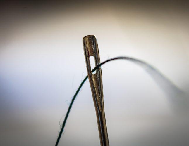 針に糸を通す写真