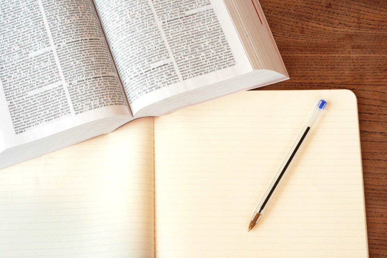 厚い本とノートの写真